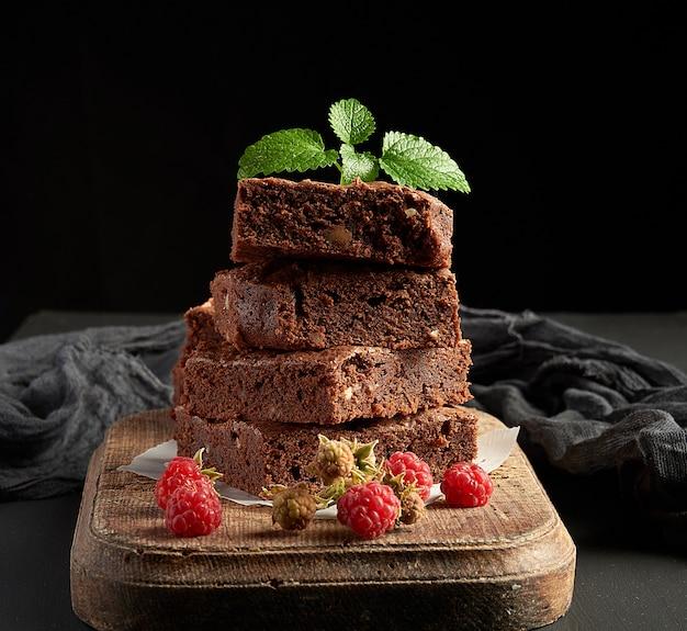 Stos pieczone kwadratowe kawałki ciasta czekoladowe brownie na brązowy drewnianą deską do krojenia