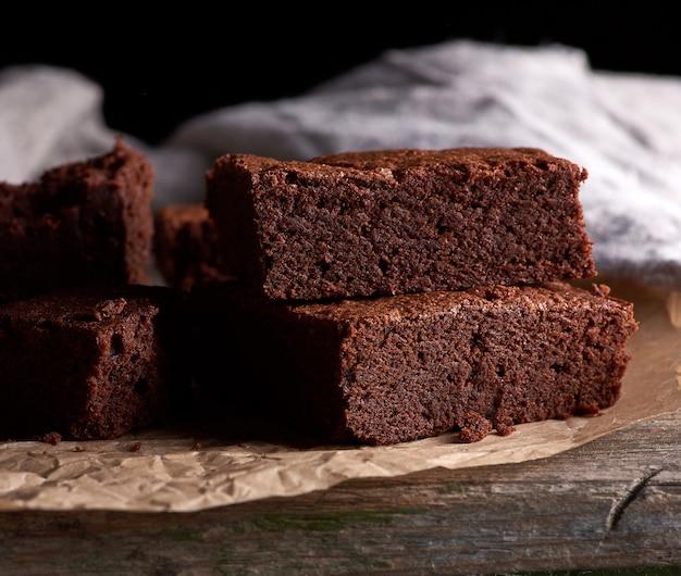 Stos pieczone kwadratowe kawałki ciasta czekoladowe brownie na brązowy pergamin