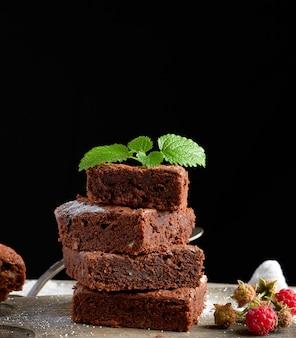 Stos pieczone kwadratowe kawałki ciasta czekoladowego brownie