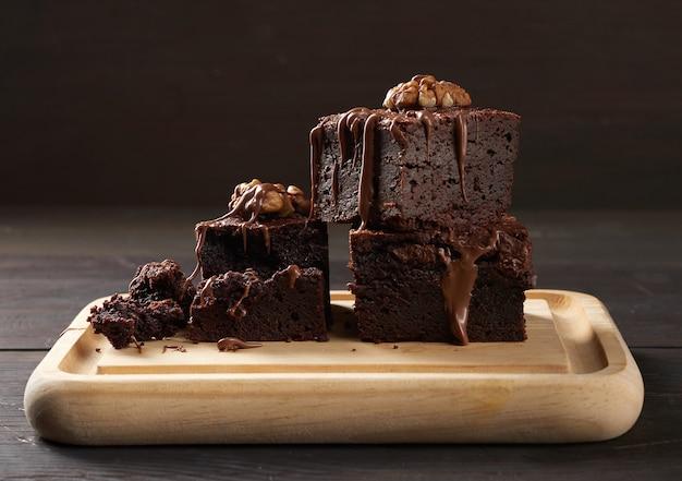Stos pieczonych kawałków ciasta czekoladowego brownie z orzechami na desce, pyszny deser, z bliska