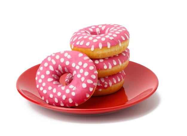 Stos pieczonych pączków z różowym lukrem na czerwonym okrągłym talerzu, jedzenie izolowane na niebieskiej powierzchni
