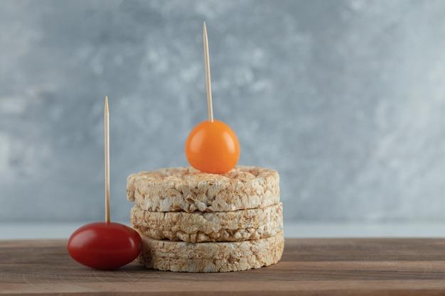 Stos pieczywa chrupkiego i pomidorków cherry na desce