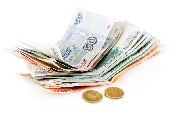 Stos pieniędzy papierowych rosyjski z dwiema monetami na białym tle