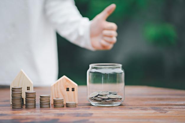 Stos pieniędzy z umieszczaniem monet w krok słoika rośnie wzrost oszczędności pieniędzy, koncepcja finansowania inwestycji biznesowych
