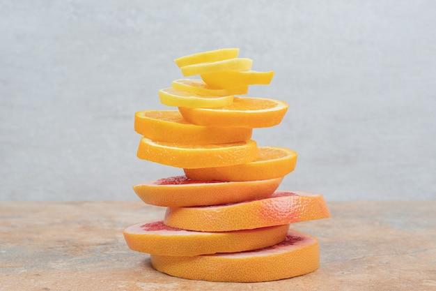 Stos plasterków cytryny, pomarańczy i grejpfruta na marmurowym stole. wysokiej jakości zdjęcie