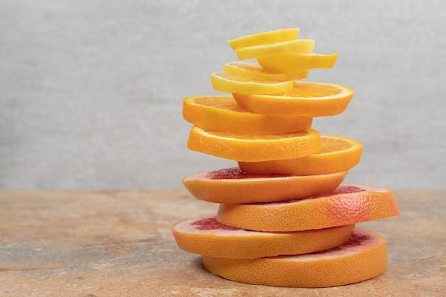 Stos plasterków cytryny, pomarańczy i grejpfruta na marmurowym stole.