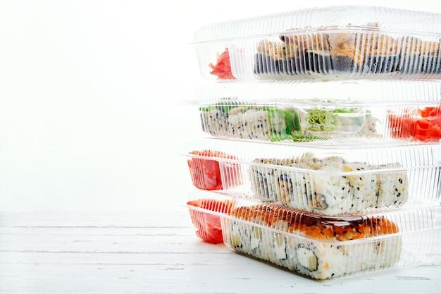 Stos plastikowych pudełek z zestawami rolek sushi. dostawa jedzenia