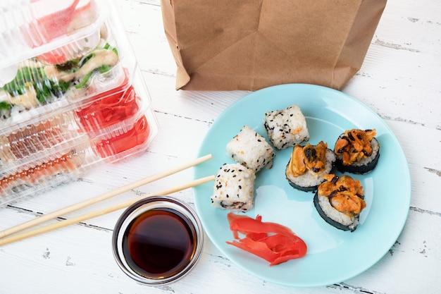 Stos plastikowych pudełek z zestawami rolek sushi, talerz z rolkami i torebka papierowa. dostawa jedzenia