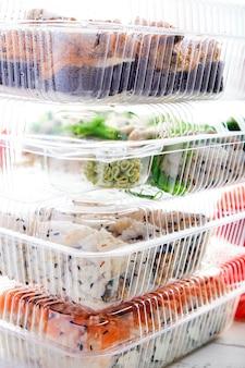 Stos plastikowych pudełek z zestawami rolek sushi
