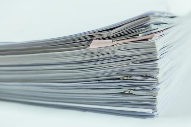 Stos plików papierowych raportów biznesowych
