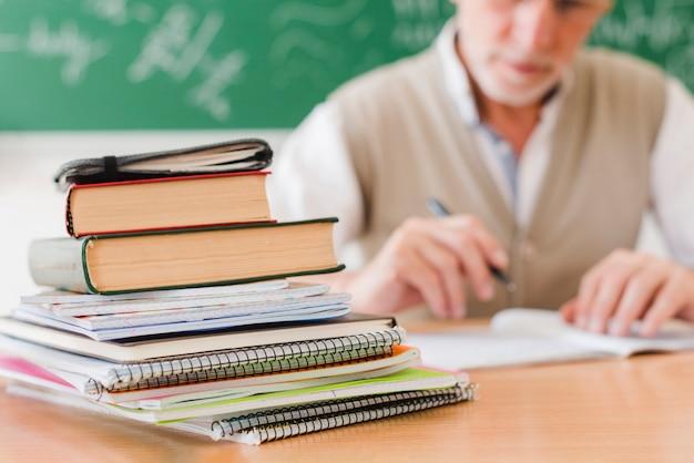 Stos podręczników ułożonych na biurku profesora w sali wykładowej
