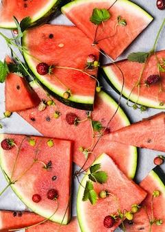 Stos pokrojonych w plasterki świeżych arbuzów i poziomek z zielonymi liśćmi