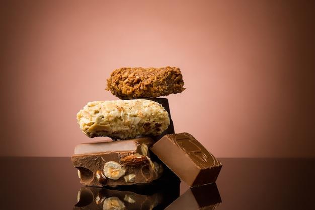 Stos połamanej czekolady na stole na brązowym tle studia
