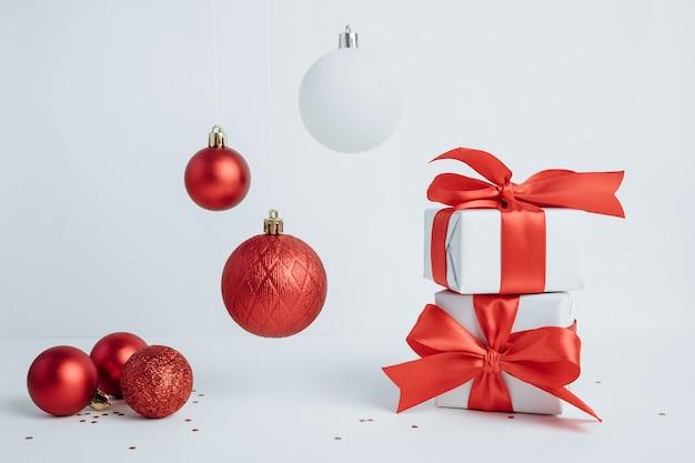 Stos prezentów świątecznych z czerwoną wstążką i wiszące ozdoby na białym tle