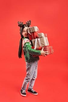 Stos prezentów trzymanych przez dziecko