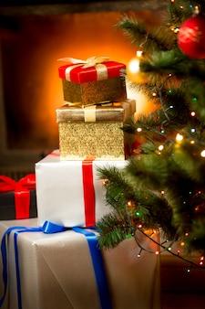 Stos prezentów w kolorowych pudełkach pod choinką