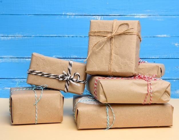 Stos prezentów zawiniętych w brązowy papier pakowy i przewiązanych liną, pudełka na niebieskim tle