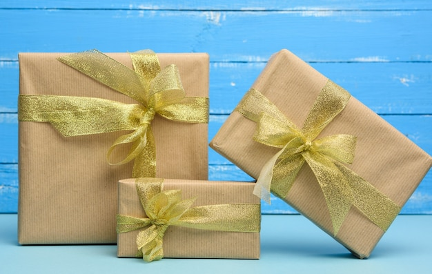 Stos prezentów zawiniętych w brązowy papier pakowy i przewiązanych złotą wstążką, pudełka na niebieskim tle