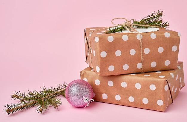 Stos prezenty pakowane w papier pakowy i świerk oddział na różowej powierzchni