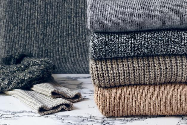 Stos przytulnych swetrów z dzianiny. koncepcja jesień-zima, swetry z wełny z dzianiny. kupie dzianinowe ubrania zimowe, swetry, dzianiny