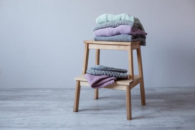 Stos przytulnych ubrań z dzianiny na drewnianej drabinie.
