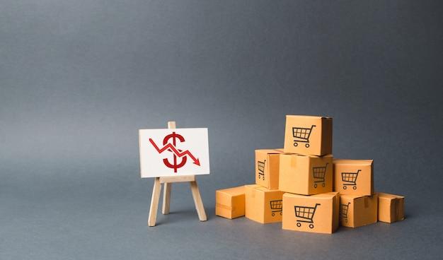 Stos pudeł kartonowych i podstawka z czerwoną strzałką w dół. spadek produkcji towarów