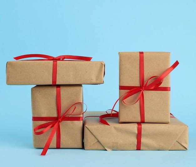 Stos pudełek owinięty w brązowy papier i związany czerwoną kokardą