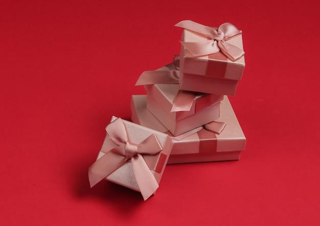 Stos pudełka z kokardkami na czerwonym tle studio. kompozycja na boże narodzenie, urodziny lub wesele.
