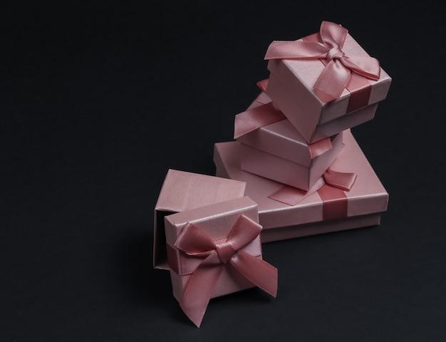 Stos pudełka z kokardkami na tle czarnego studia. kompozycja na boże narodzenie, urodziny lub wesele.