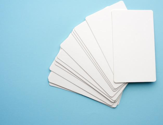 Stos pustych wizytówek prostokątnego białego papieru na niebieskim tle
