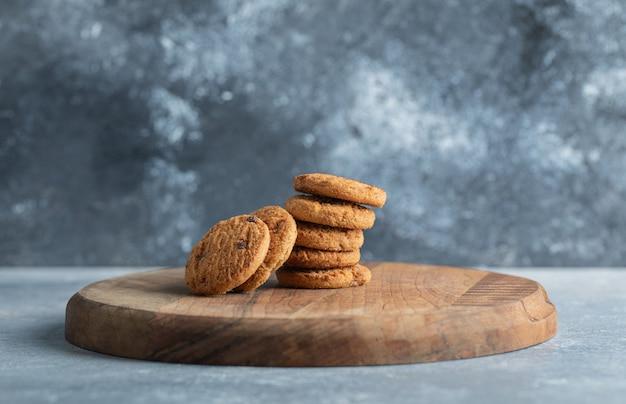 Stos pysznych ciasteczek z kawałkami czekolady na drewnianej desce