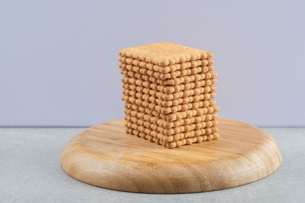 Stos pysznych krakersów na drewnianym kawałku.