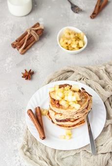 Stos pysznych naleśników jabłkowych ze smażonymi karmelizowanymi jabłkami i przyprawami.
