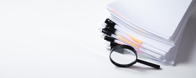 Stos raportów papierowych dokumentów z lupą. pojęcie biznesu i wyszukiwania.