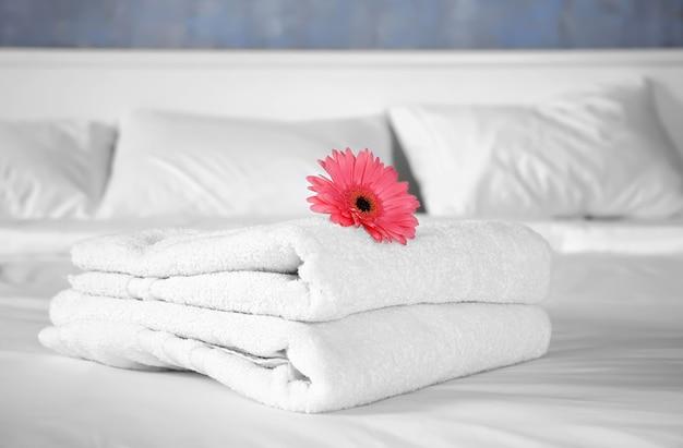 Stos ręczników i kwiat na łóżku w pokoju hotelowym