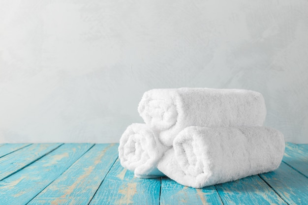 Stos ręczników kąpielowych na drewnianym stole z miejsca na kopię