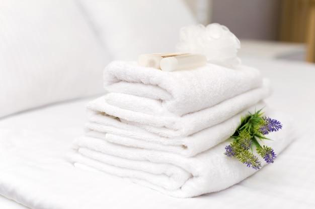 Stos ręczników z kwiatowym wystrojem w pokoju hotelowym