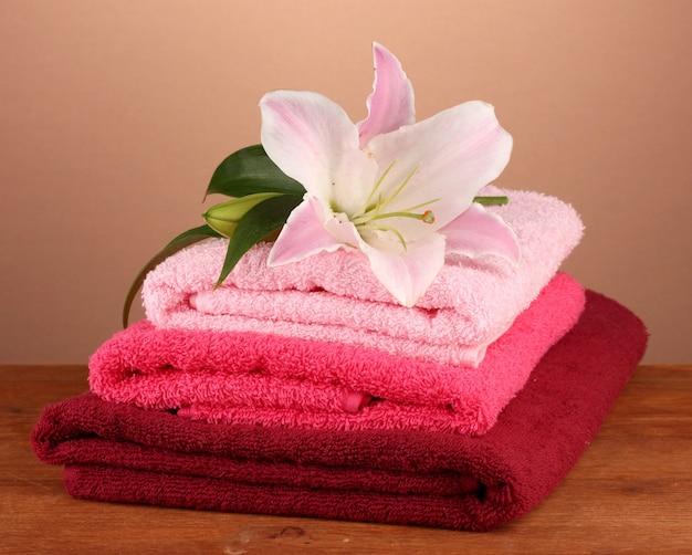 Stos ręczników z różową lilią na brązowym stole