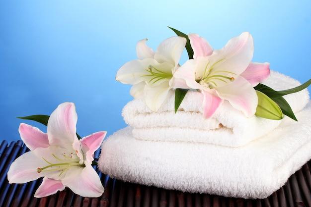 Stos ręczników z różową lilią na niebieskiej powierzchni