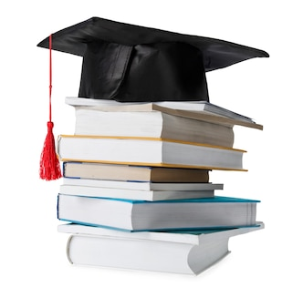 Stos różnokolorowych książek z czapką ukończenia szkoły