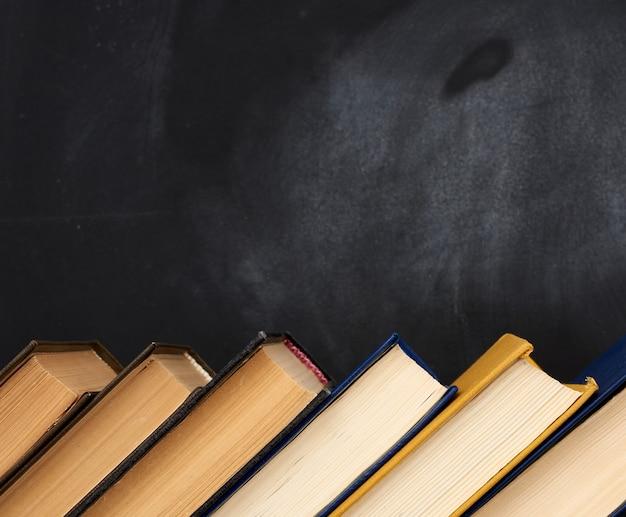 Stos różnych książek na tle pustej czarnej tablicy kredą