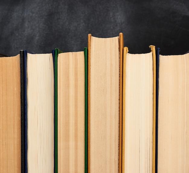 Stos różnych książek w przestrzeni pustej czarnej tablicy kredą