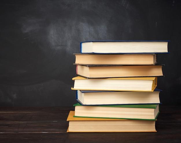 Stos różnych książek w twardej oprawie na przestrzeni pustej czarnej tablicy kredą
