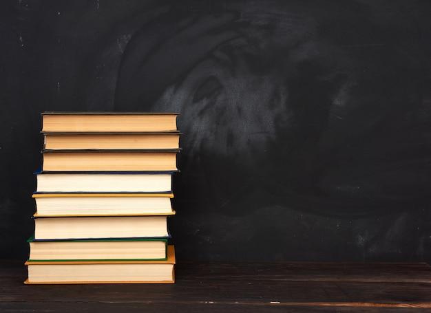 Stos różnych książek w twardej oprawie na tle pustej czarnej tablicy kredą