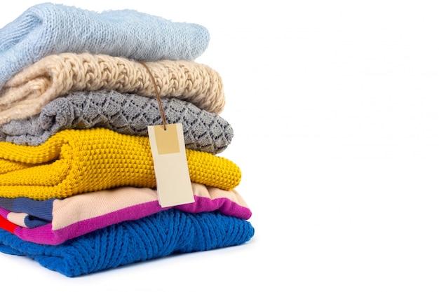 Stos różnych swetrów na białym