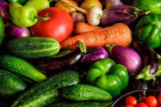 Stos różnych warzyw na stole, krople wody na świeże warzywa. żniwa z ogrodu. witaminy, długowieczność, ekologia