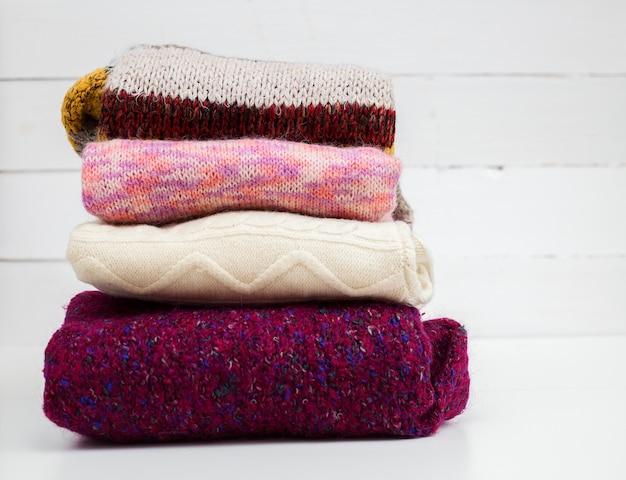 Stos różnych wełniane swetry w białej ścianie