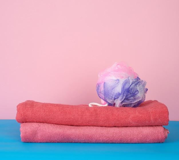 Stos różowo złożonych ręczników i plastikowej myjki
