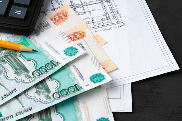 Stos rubli rosyjskich na planach z kalkulatorem. remont, koncepcja kosztów budowy