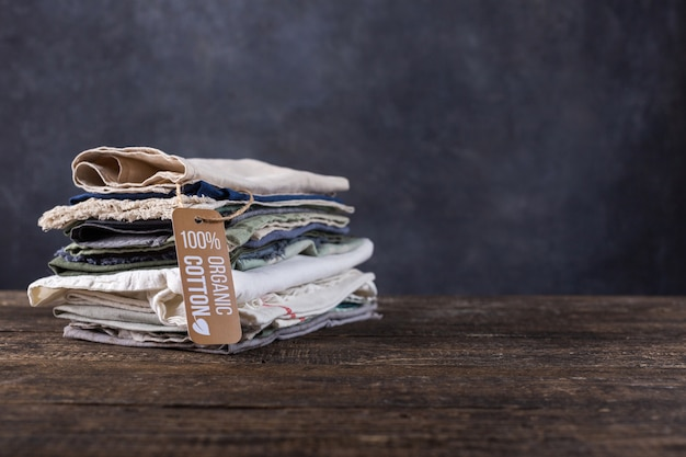 Stos rzeczy leżą na drewnianym stole. bawełniane, lniane przedmioty w pastelowych kolorach koszule, strzępy materiału, szale.